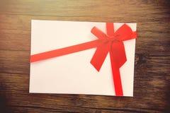 Gåvakort på det rosa vita gåvakortet för träbakgrund som dekoreras med den röda bandpilbågen till året för ferie för glad jul det royaltyfri bild
