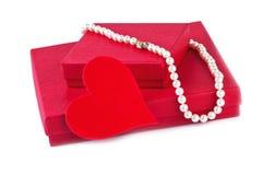 Gåvan boxas med det röda hjärta- och pärlahalsbandet på vit Royaltyfri Foto