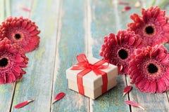 Gåvan eller gåva för den moder- eller kvinnans dagen som dekoreras med den härliga gerberatusenskönan, blommar på tappningträbakg royaltyfri fotografi