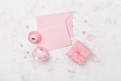 Gåvan eller gåva, rosa färgpappersmellanrumet och ranunculusen blommar på den vita bästa sikten för tabellen för att gifta sig de arkivbilder