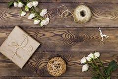 Gåvan eller gåvaasken som slås in i den kraft papper och blomman, tvinnar och sax på träbakgrund från över Lekmanna- lägenhet royaltyfria foton