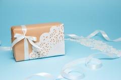 Gåvan för Kraft papper som dekoreras med, snör åt servetten på en blå pappers- bakgrund letters amerikansk för färgexplosionen fö royaltyfri fotografi