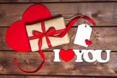 Gåvan och ord`en älskar jag dig ` på en träbakgrund valentiner för daghjärtared för dageps för 8 kort valentin för mapp bland ann Royaltyfria Bilder
