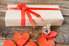 Gåvan packas i Kraft papper, och bundet med ett rött band steg Gåvan som omges av dekorativa hjärtor en, är en vigselring med royaltyfria foton