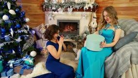 Gåvan som ger sig, vänner hälsar sig med jul gåvan, syster framlägger gåvan för det nya året, flickan som förvånas med en gåvaask stock video