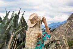 Gåvauppsättning, stearinljus, stenar, brunnsortskönhetsmedel, gåvaask och gåvakort På en röd bakgrund Härlig blond kvinna i hatt, arkivfoto