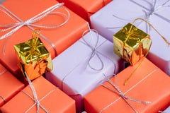 Gåvor överst av gåvor som slås in i rött och lila papper royaltyfri foto