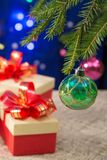 Gåvor för ` s för nytt år bredvid den dekorerade julgranen på ett mörker - blå bakgrund med suddiga ljus vertikalt Arkivfoton