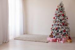 Gåvor för träd för nytt år för kort för hälsning för vitt rum för jul inre royaltyfri fotografi