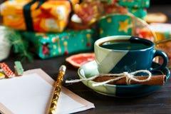 Gåvor för vänner och familj i apelsinen och dokument med olika förslag, notepad, kopp kaffe på träbakgrunden shopping arkivfoton