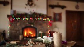 Gåvor, gåvor och förpackande material: inpackningspapper, granträdfilialer, kottar och band på tabellen spis stock video