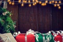 gåvor och leksaker på träbräden dekorerade ljus arkivbilder