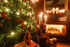 Gåvor på julgranen Julafton vid levande ljus klassiska lägenheter med en spis Arkivbild