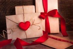 Gåvor som slås in med ett rött band En bokstav med en röd hjärta Arkivfoto