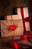 Gåvor som slås in med ett rött band En bokstav med en röd hjärta Arkivfoton