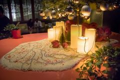 Gåvor under julgranen i omgivande vardagsrum med spisen arkivbild