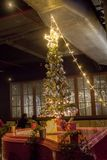Gåvor under julgranen i omgivande vardagsrum med spisen royaltyfria foton