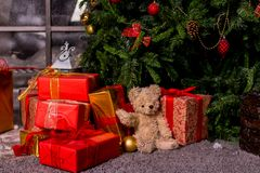 Gåvor under julgranen, leksakbjörnen och askarna, begreppet av ett nytt år för slags tvåsittssoffahem Väntande jultomten för björ royaltyfria foton