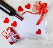 Gåvor, vin, två exponeringsglas, hjärtor och ett ark för texten på taПоen Ð'арки, ¾ för ½ Ð för Ð-² иÐ, Ð'Ð-²Ð° бР¾ ка Fotografering för Bildbyråer