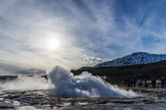 Géiser que entra en erupción la agua caliente durante puesta del sol Imagen de archivo libre de regalías