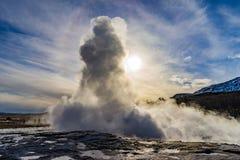 Géiser que entra en erupción la agua caliente durante puesta del sol Foto de archivo libre de regalías