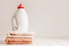 Gélifiez pour la blanchisserie lavant dans une bouteille en plastique anonyme blanche, en tenant sur les serviettes colorées fraî Photographie stock libre de droits