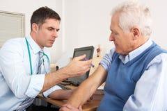 Généraliste britannique injectant l'homme aîné dans la chirurgie Image libre de droits