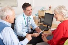 Généraliste britannique parlant aux couples aînés dans la chirurgie Photographie stock