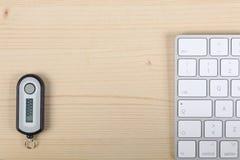 Générateur de mot de passe d'opérations bancaires par télématique sur un bureau en bois, un clavier d'ordinateur avec l'espace de images stock