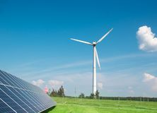 Générateur de vent de l'électricité de trois lames et de fond de panneaux solaires des nuages et d'une herbe verte de ciel bleu photos stock