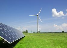 Générateur de vent de l'électricité de trois lames et de panneaux solaires d'une batterie de nuages de cellules photo-électriques image libre de droits