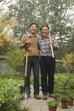 Génération deux travaillant dans le jardin, souriant et tenant des outils de jardinage Images stock