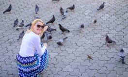 Générosité de part Place de ville de détente de femme blonde de fille et pigeons de alimentation Miettes de lancer de touriste ou photographie stock libre de droits
