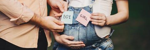 Género del bebé Mamá y papá con las tarjetas del MUCHACHO y de la MUCHACHA Imagen de archivo