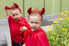 Gêmeo idêntico da criança disfarçado como o diabo que faz uma carranca com o irmão no fundo macio do foco fotos de stock