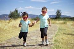 Gêmeos bonitos que saltam ao longo do trajeto no campo Imagens de Stock Royalty Free