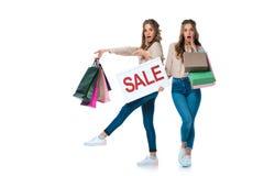 gêmeos chocados com sinal da venda que apontam em sacos de compras imagens de stock