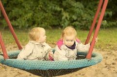 Gêmeos das irmãs que balançam em um balanço foto de stock
