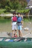 Gêmeos felizes aprontam-se para canoe imagem de stock