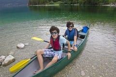 Gêmeos felizes aprontam-se para canoe no lago Bohinj, Eslovênia Fotografia de Stock Royalty Free