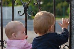 Gêmeos na mão de ondulação da porta Imagens de Stock