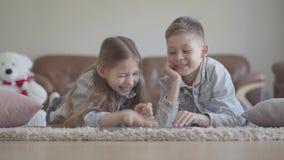 Gêmeos pequenos adoráveis menino do retrato e mentira da menina no tapete e em olhar algo engraçado no computador, rindo e video estoque