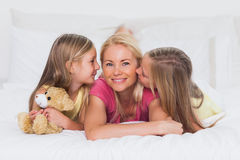 Gêmeos que beijam sua mãe na cama Fotografia de Stock
