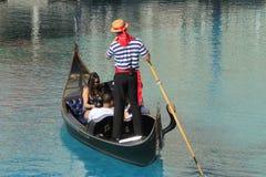 Góndola con los turistas en un canal, un hotel turístico veneciano y un casi fotos de archivo libres de regalías