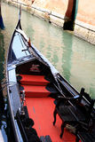 Góndola negra y roja brillante en el canal veneciano Imagen de archivo