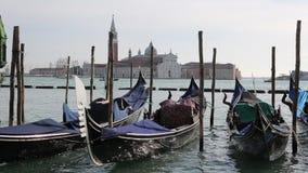 Góndolas para transportar a los turistas amarrados en Venecia y el santo George Church en el fondo