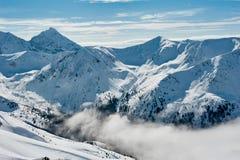 Góra i doliny zakrywający z śniegiem i chmurami Zdjęcie Royalty Free