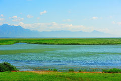 Góra i jezioro z pogodnym niebem Obrazy Royalty Free