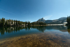 Góra i sosny odbija na wysokogórskim jeziorze obrazy stock