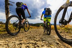Góra jechać na rowerze kobiety i mężczyzna jazdę na rowerach przy zmierzch górą fotografia stock